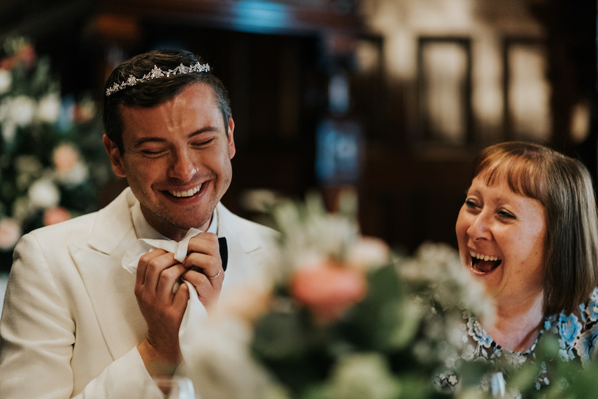 Groom wearing tiara and laughing on wedding day