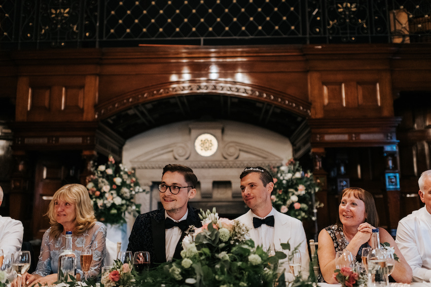 Groom and groom at wedding reception table