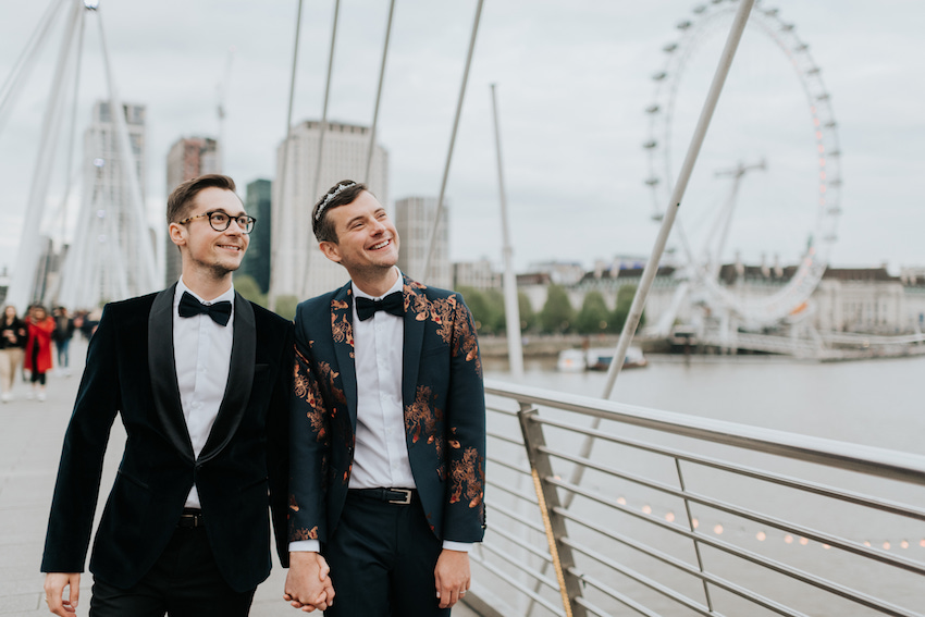 Groom and groom on bridge overlooking river Thames with London Eye behind