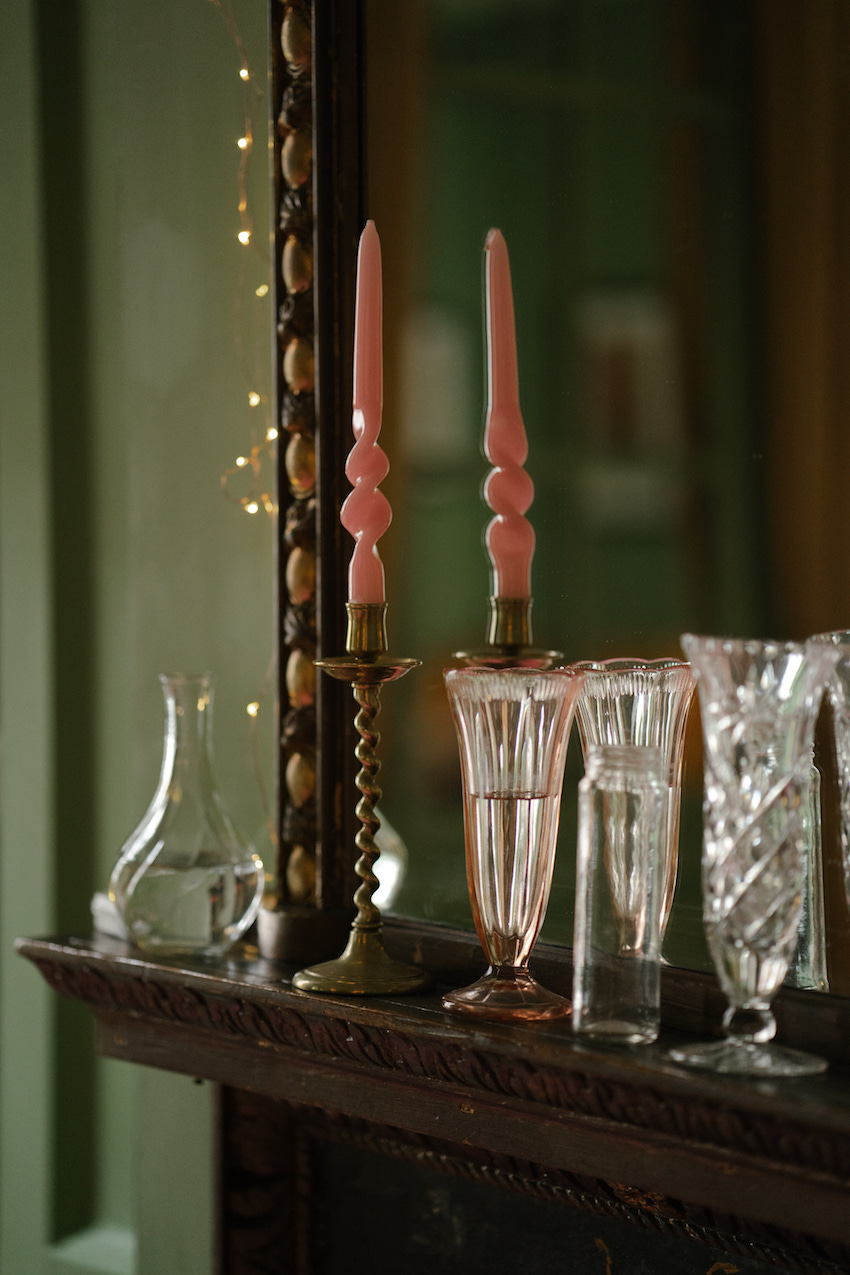 candlesticks on mantelpiece in front of mirror