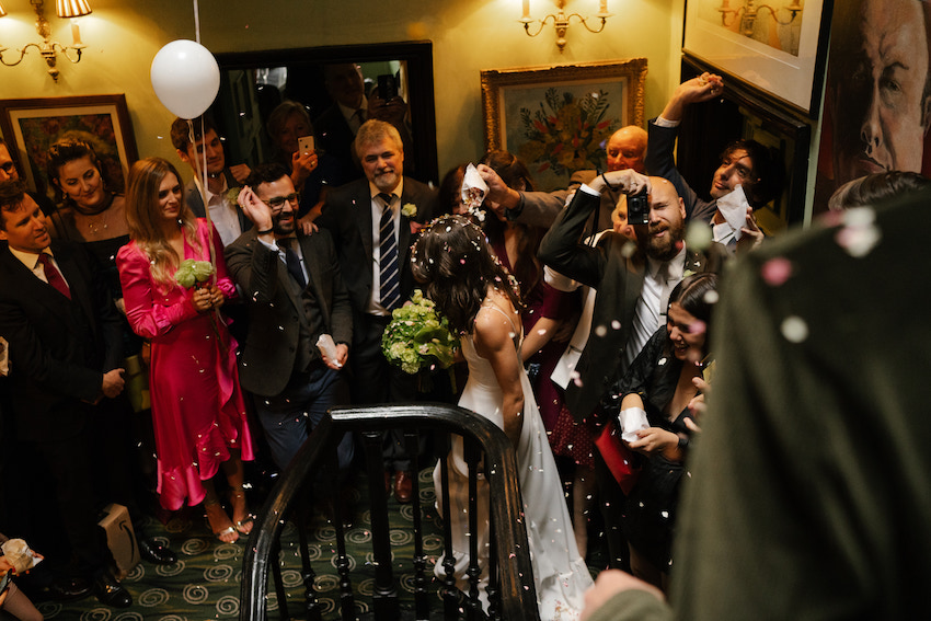 Bride coming downstairs in a confetti shower