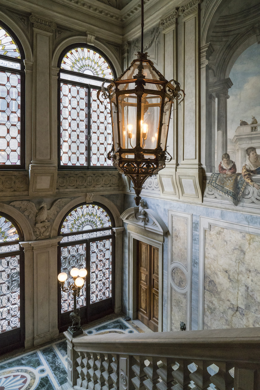 Aman, Venice, interior of building with stained glass windows and grand staircase