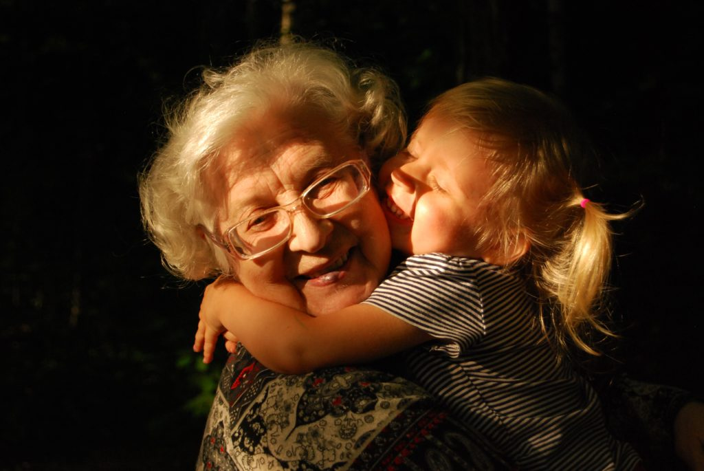 Young girl with blond hair hugging her grandmother in the sunshine