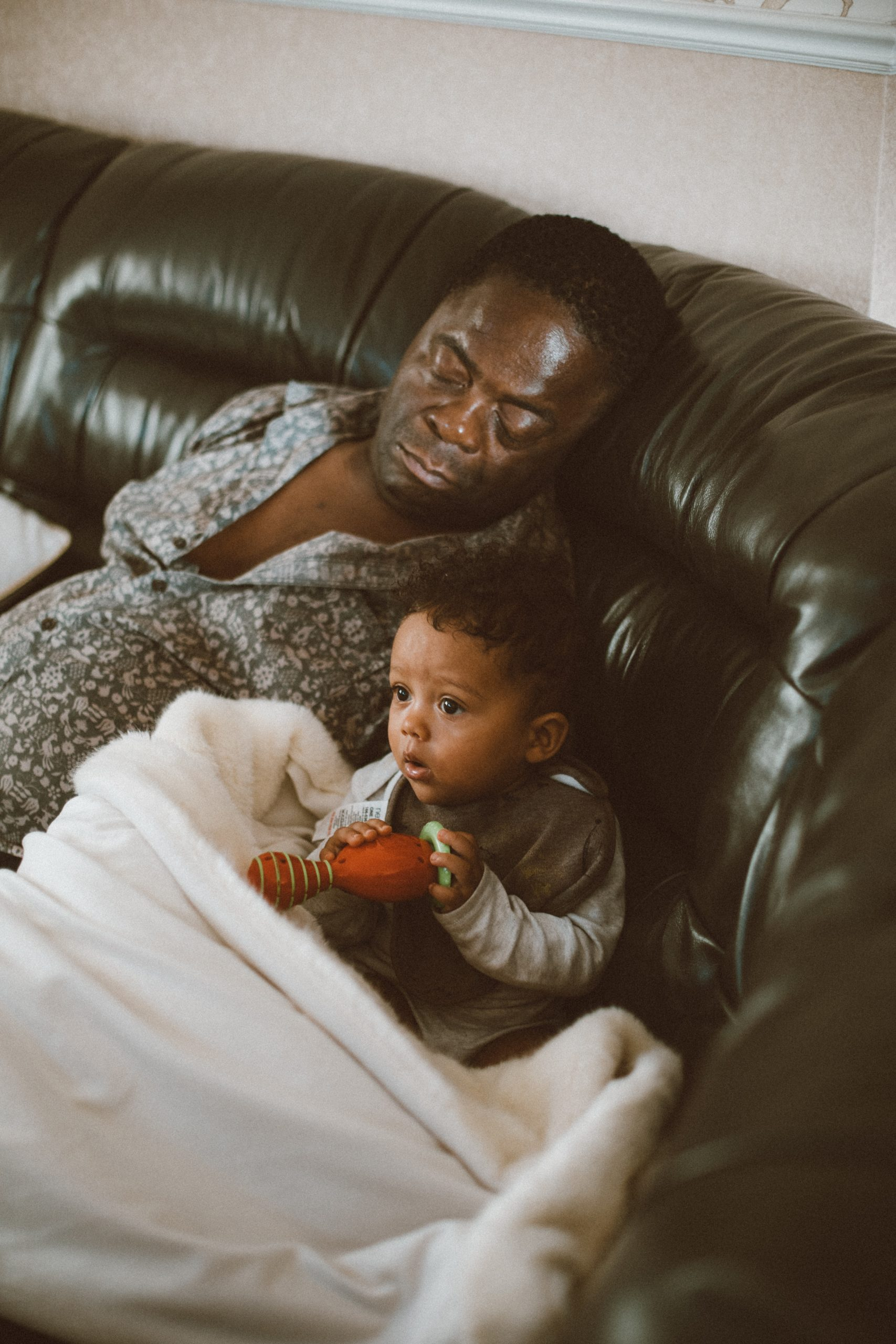 Young toddler sitting on sofa next to his sleeping grandfather