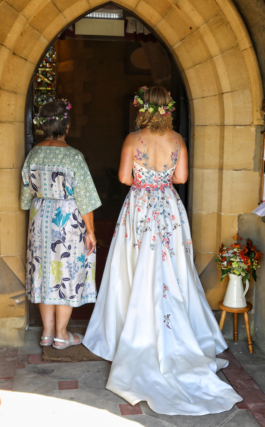 Bride and her mother, standing with backs to camera at entrance to village church