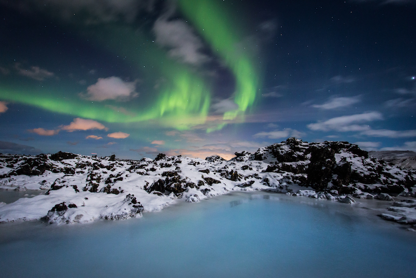 Northern Lights, view over snow-covered mountains and lagoon, Iceland
