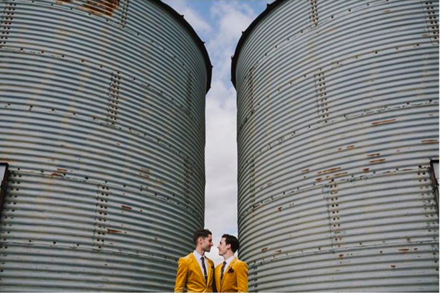 Image of gay couple in matching mustard suits standing by two huge water tanks looking in to each others eyes