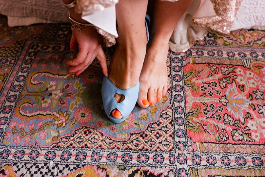 Bride putting on a pale blue open toe show against an dusky oink patterned rug