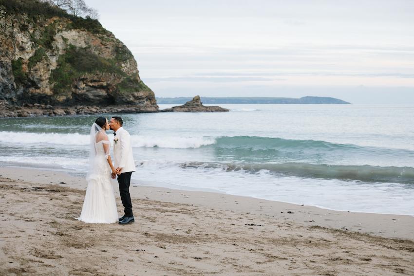 Bride and Groom kissing on Porthpean beach, Cornwall