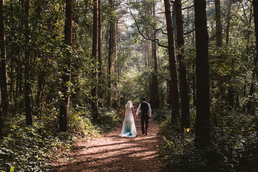 Photo of couple on wedding day, from behind, walking through forest holding hands
