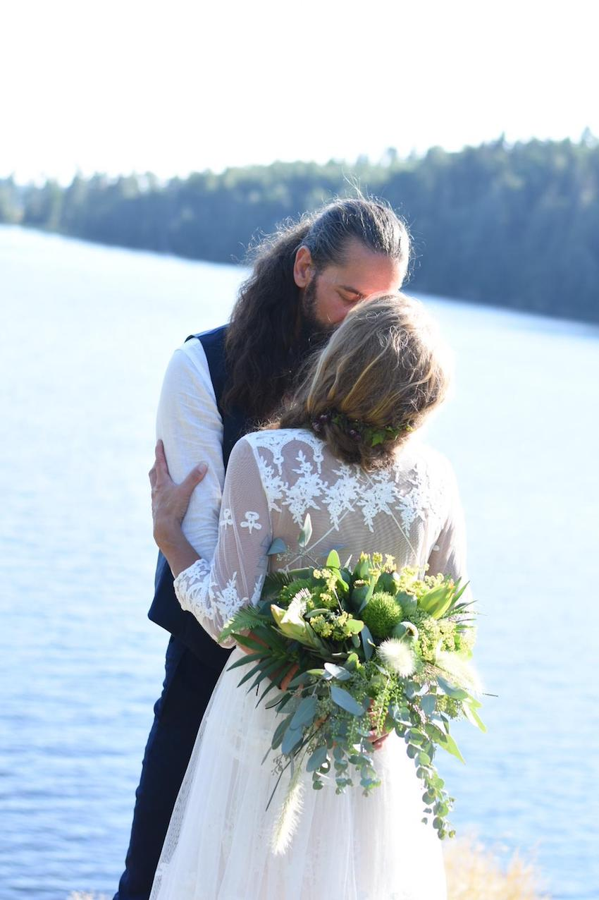 Bride and Groom kissing by the side of a lake at their small outdoor wedding in Sweden