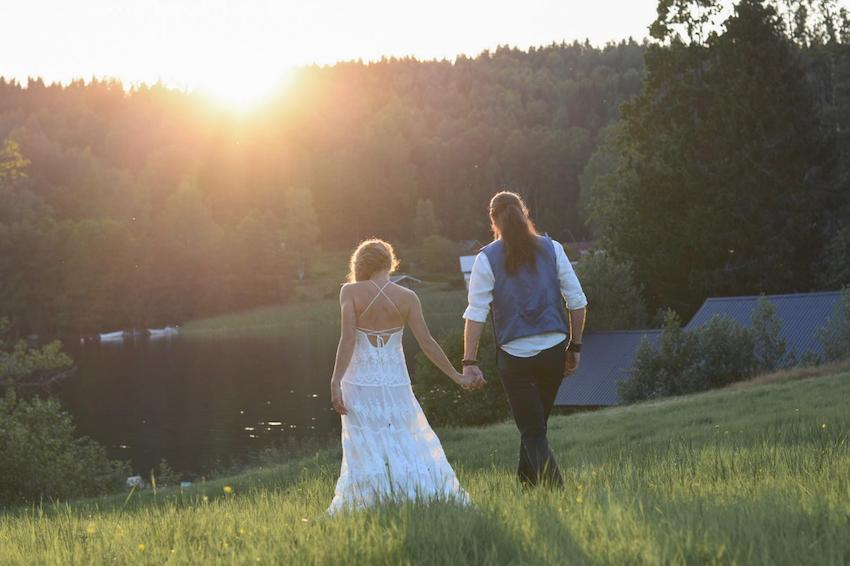 Bride and Groom walking through fields towards sunset at their small outdoor wedding in Sweden, August 2020