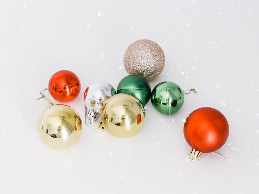 multicoloured Christmas baubles laying on white background