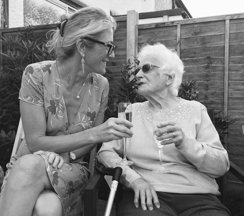 Grandmother and granddaughter enjoying a glass of champagne in garden