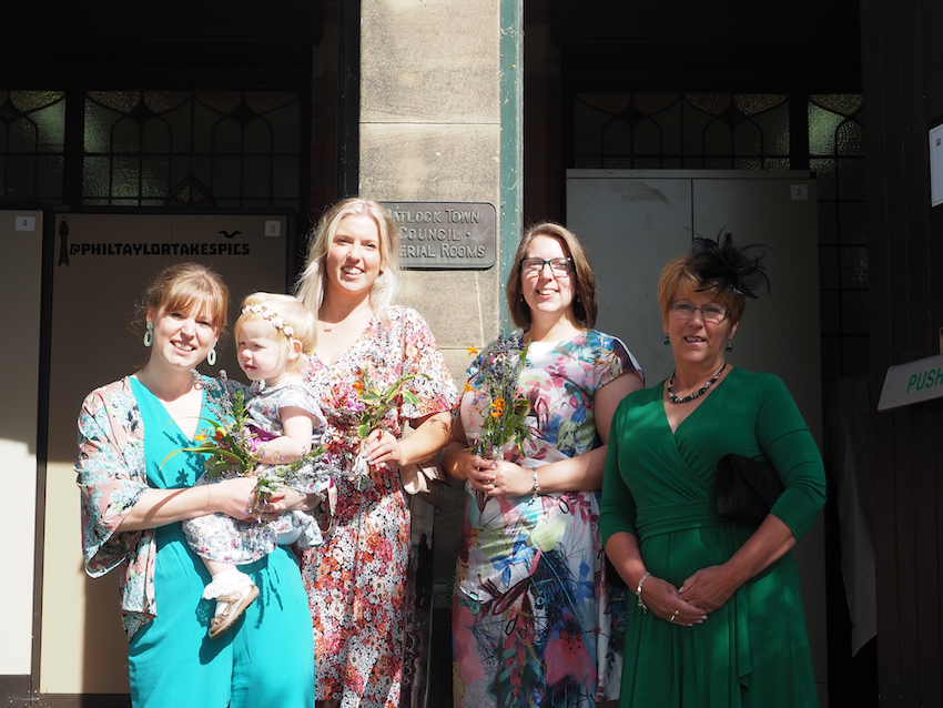 Bride and female relatives on steps of wedding venue in sunshine