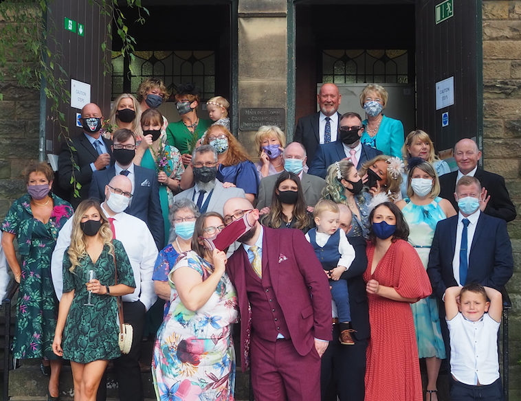 Group wedding shot with all guests in masks during 2020 pandemic