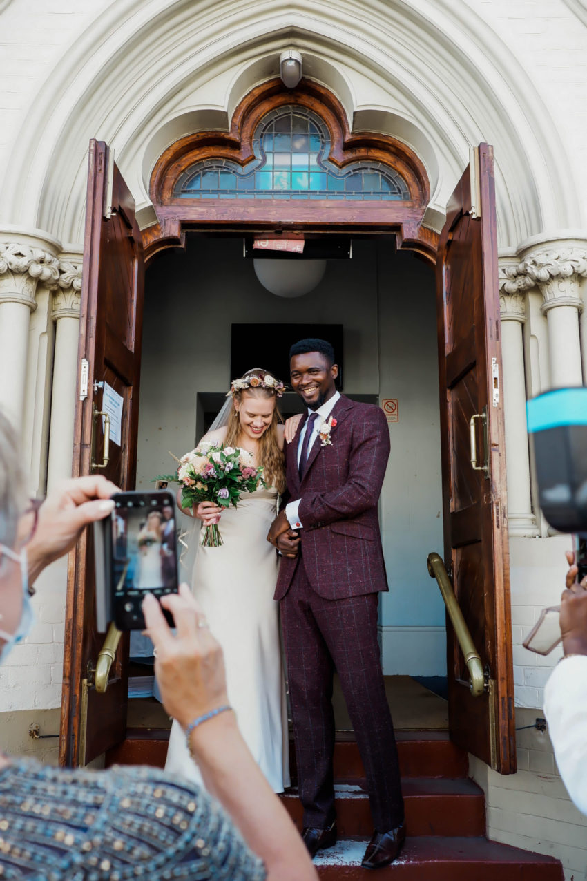 Bride and Groom smiling for camera outside church