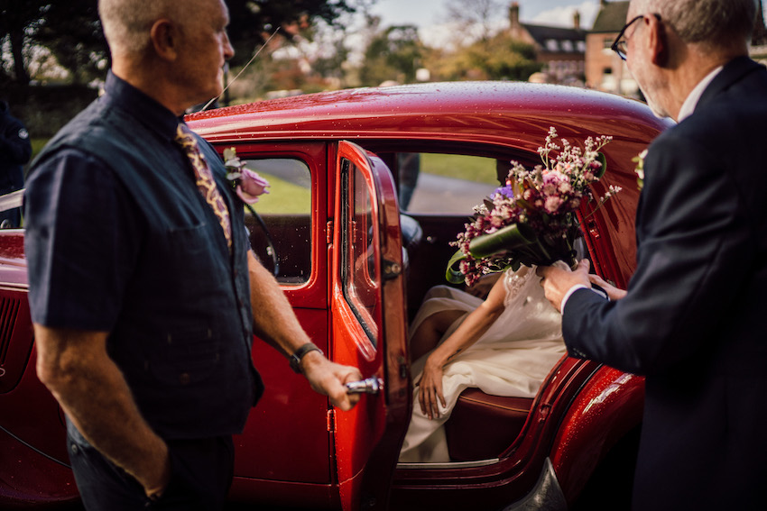 bride sitting back of red car with her father holding her bouquet