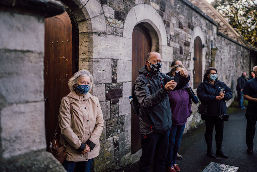 guests at wedding outside church in winter with masks on