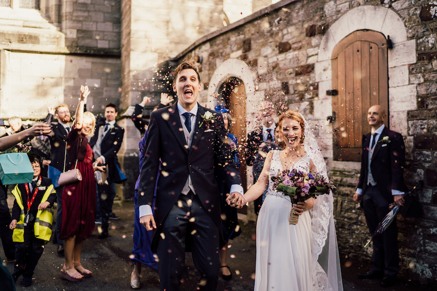 bride and groom outside church under shower of confetti