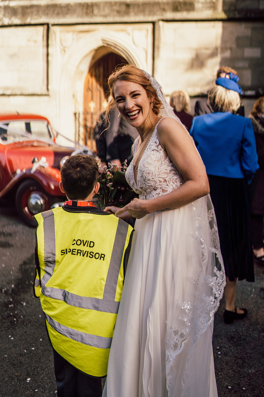 "bride with little boy dressed in ""Covid supervisor"" high vis jacket"
