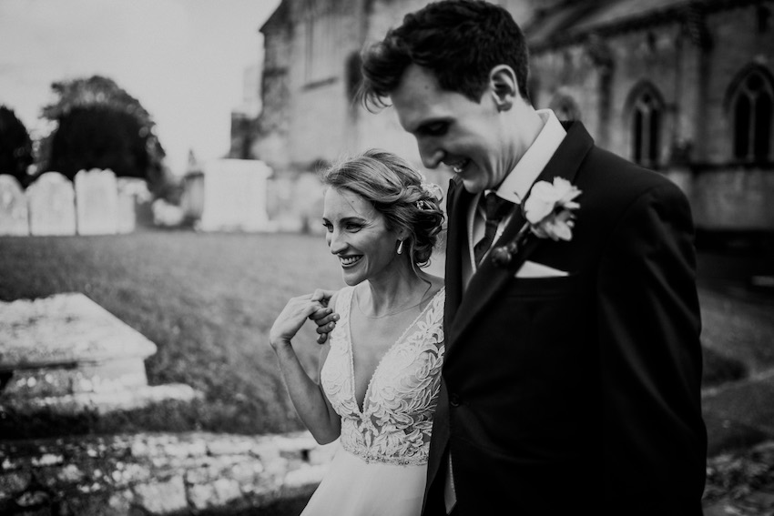 Bride and groom strolling outside church - black and white photo