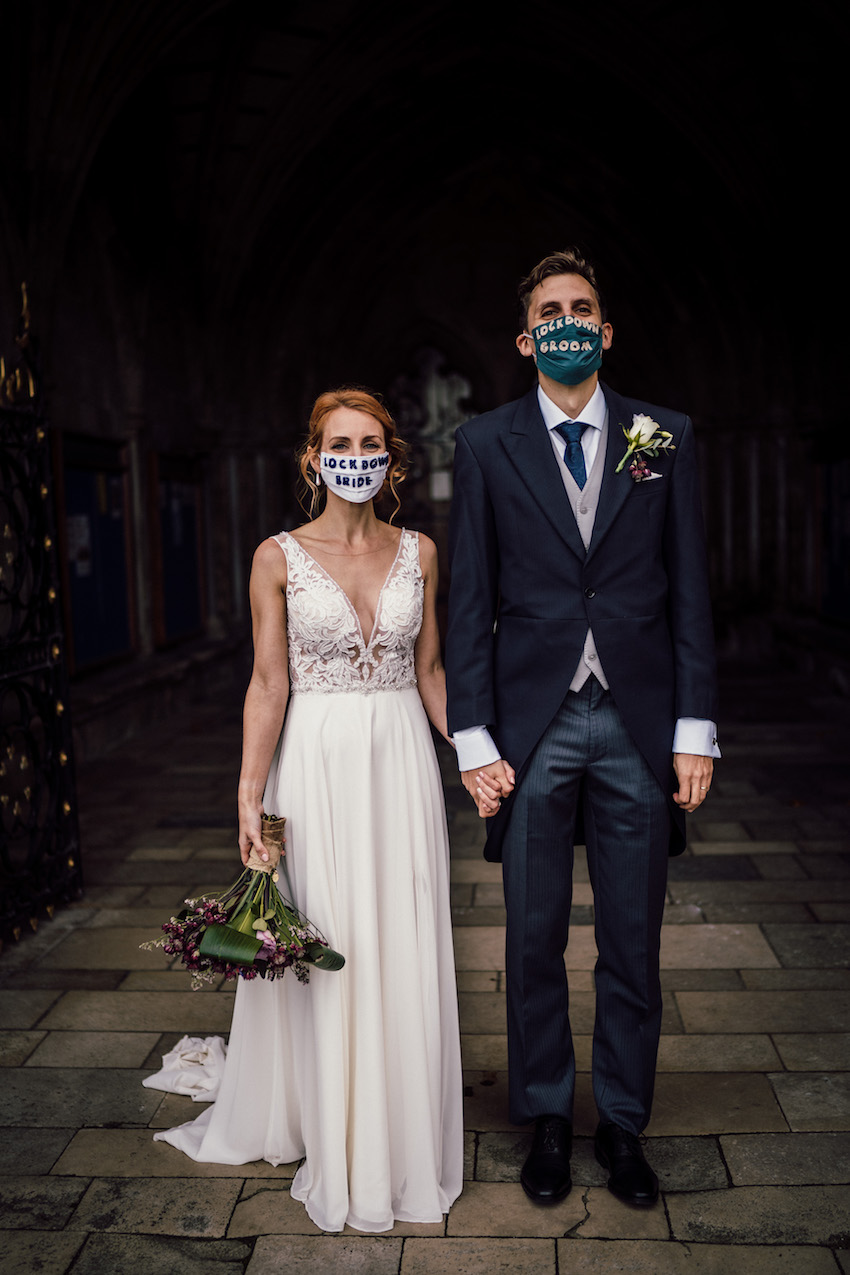 Bride and Groom wearing Covid-19 masks standing in church doorway