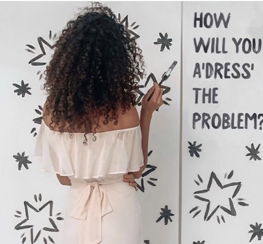 "Woman with black curly hair facing wall reading writing on wall saying ""How will you a 'dress' the problem?"""