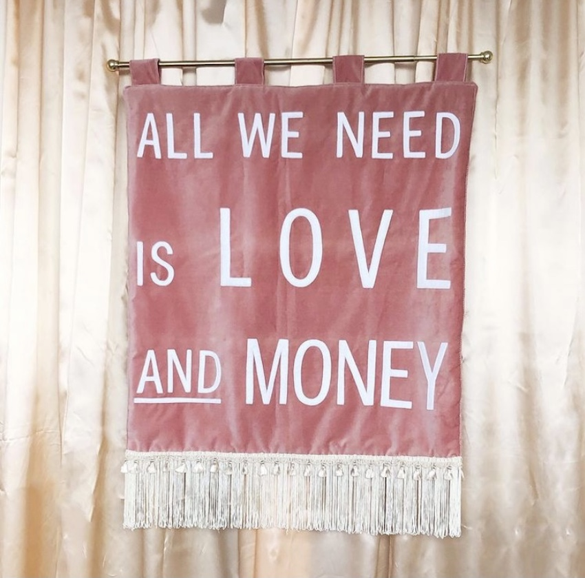 "Pink wall hanging reading ""All we need is love and money"""