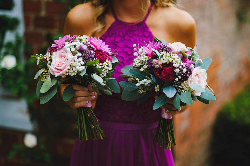 close up of bridesmaid holding a bouquet of pink flowers in each hand