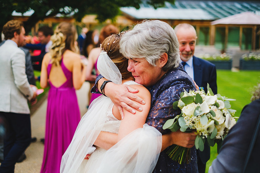 Bride hugging mother after wedding ceremony