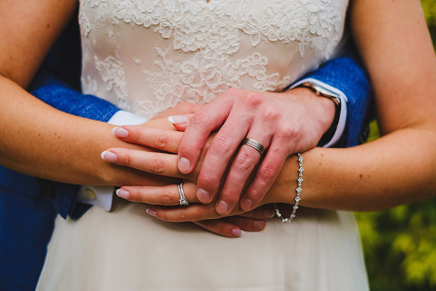 bride and grooms hands joined around brides waist