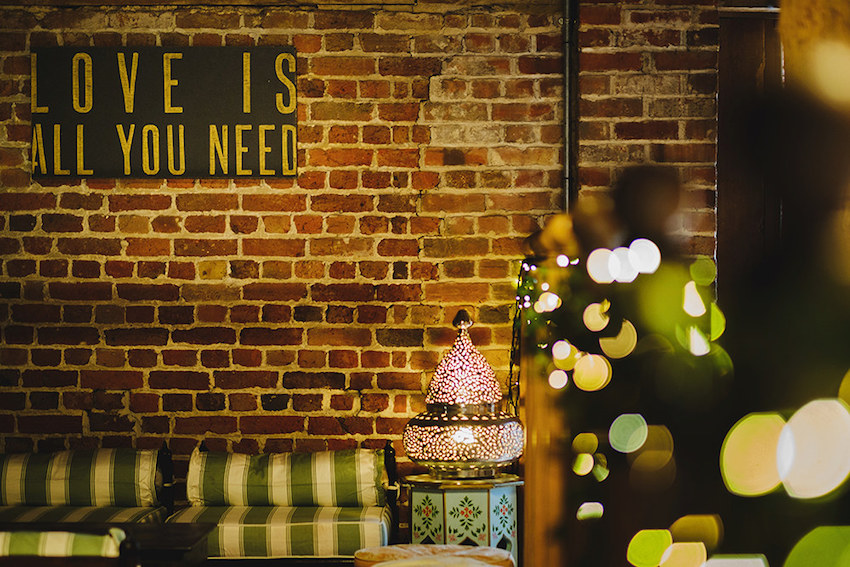 Love is all you need sign on brick wall at wedding reception