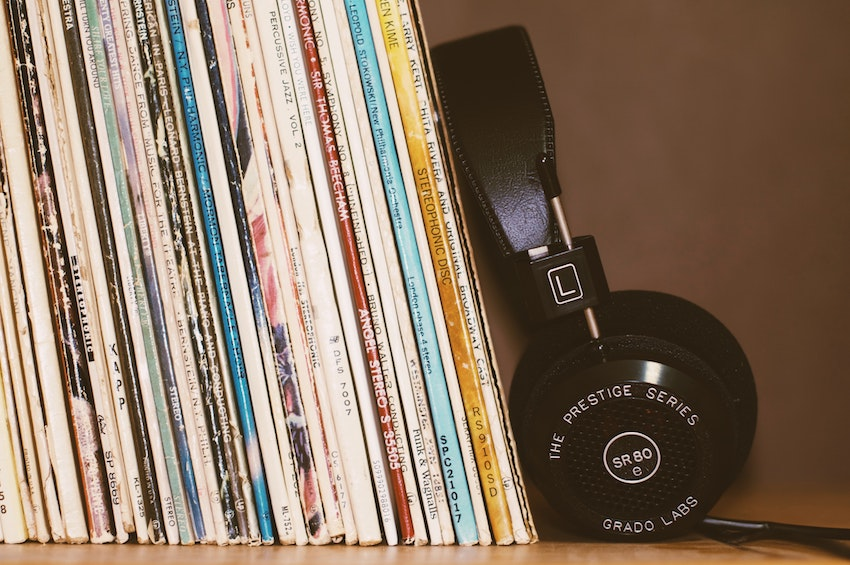 Vinyl records leaning on bookshelf with headphones