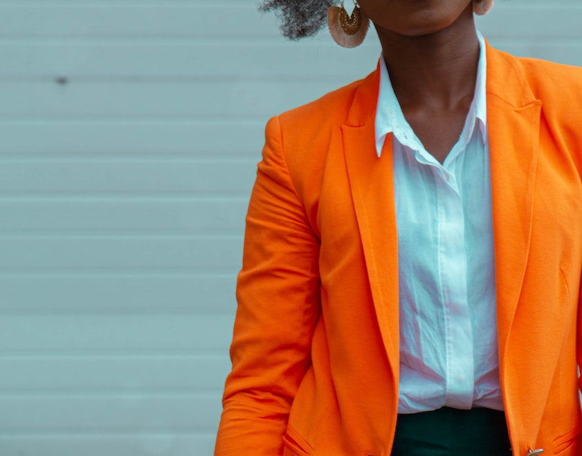 black woman wearing orange blazer and white shirt