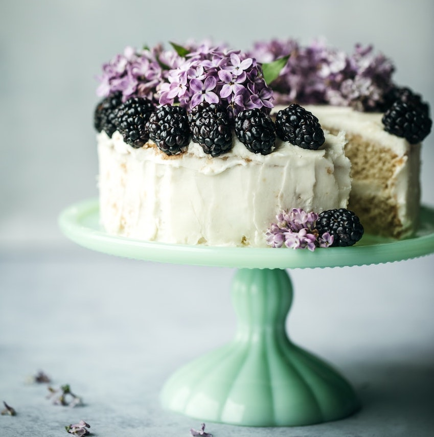 cake decorated with blackberries and lilac flowers