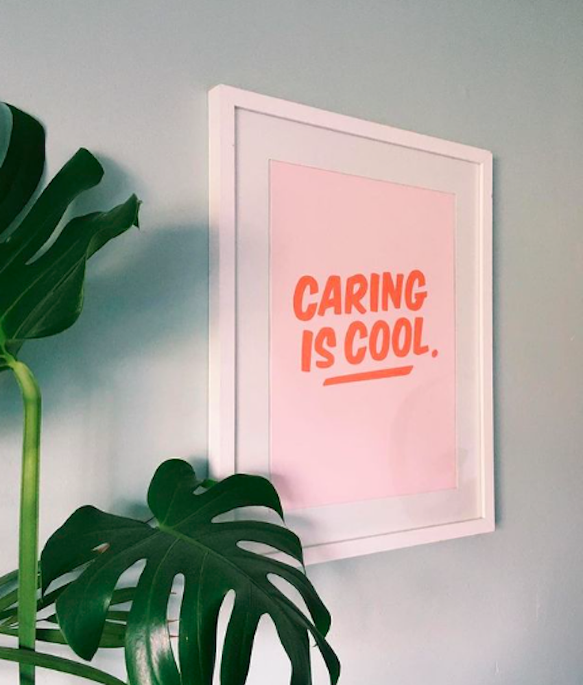 Caring is Cool print framed and displayed on wall next to plant