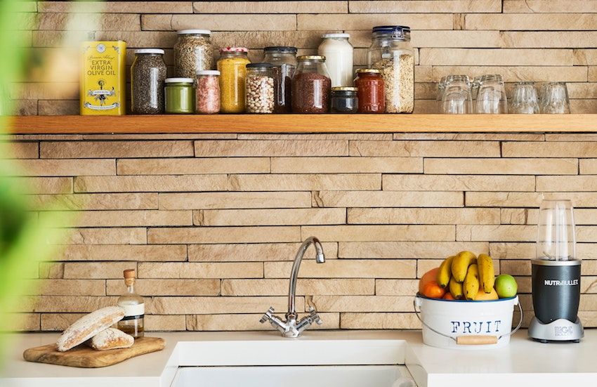 Kitchen sink with shelf above with jars of spice and herbs