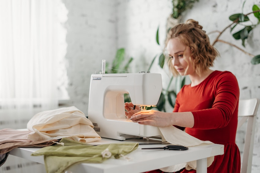 Woman wearing red top sitting and using sewing machine