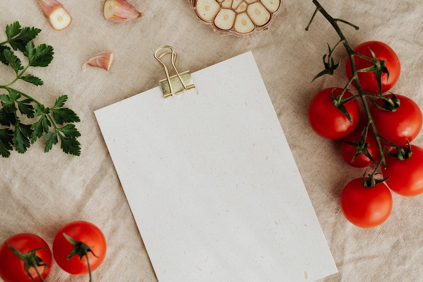 Blank note paper with gold bulldog clip on table with vegetables laid out around