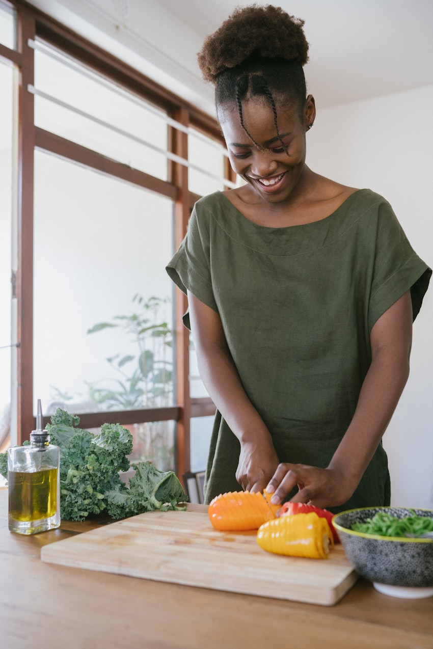 black woman cutting vegetables on chopping board in kitchen