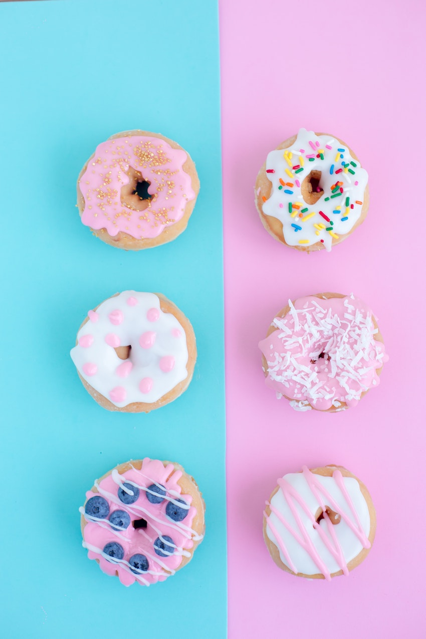 flatlay of decorated doughnuts on pink and blue background
