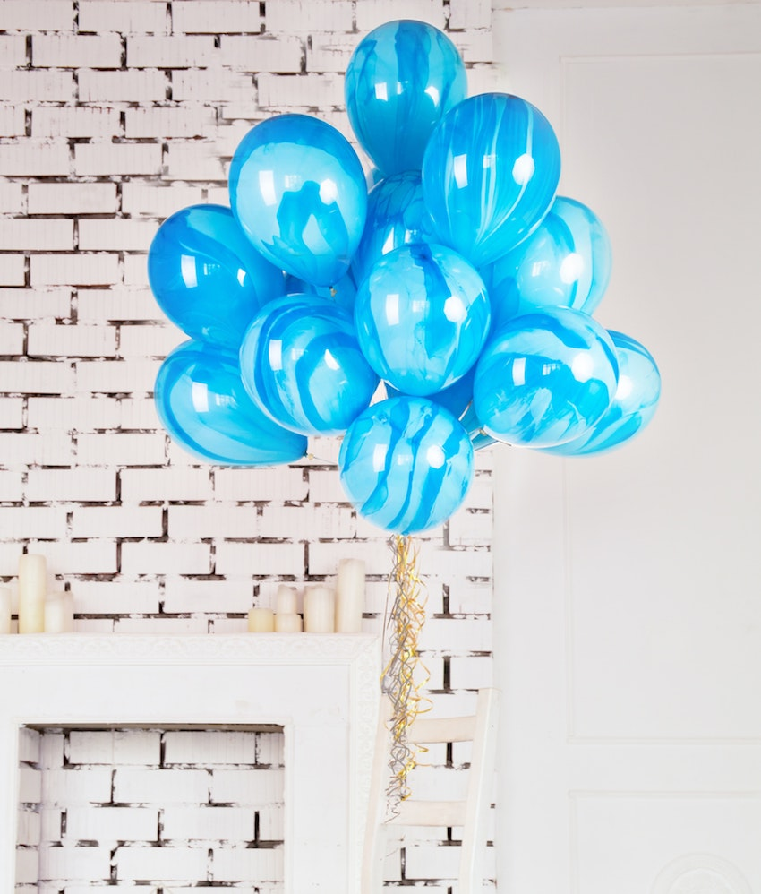 big bunch of blue balloons against white brick background