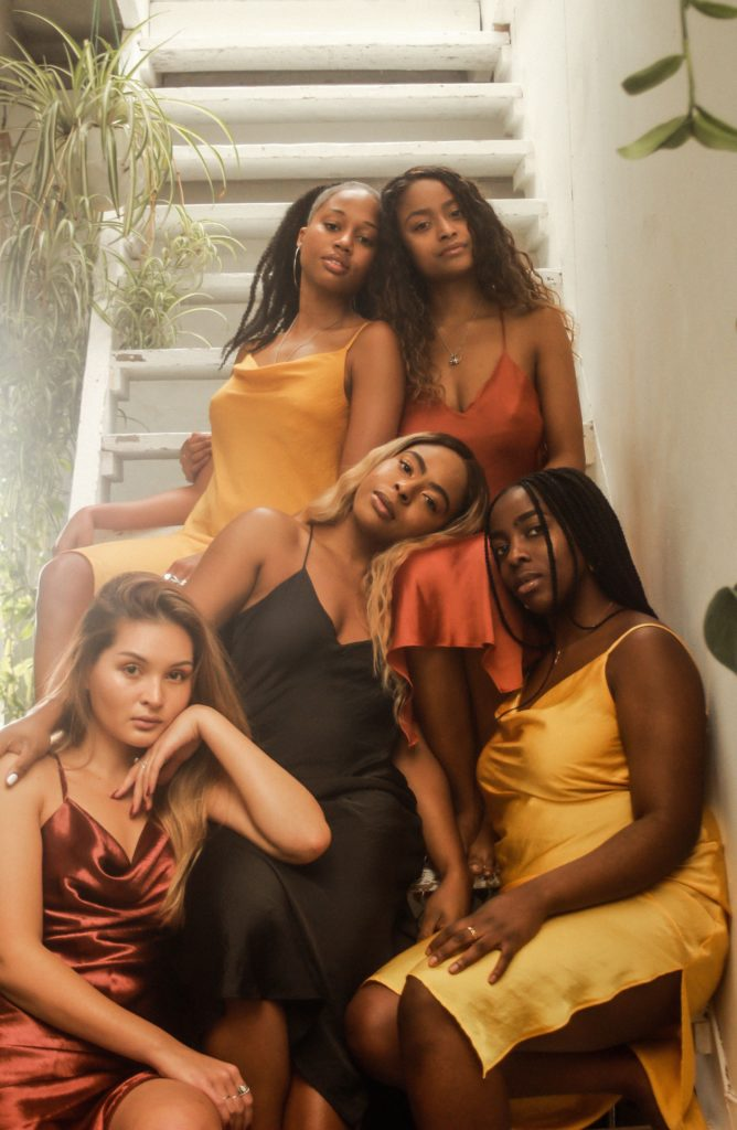 Tiwa and 4 other women are sat on stairs in silky slip dresses.