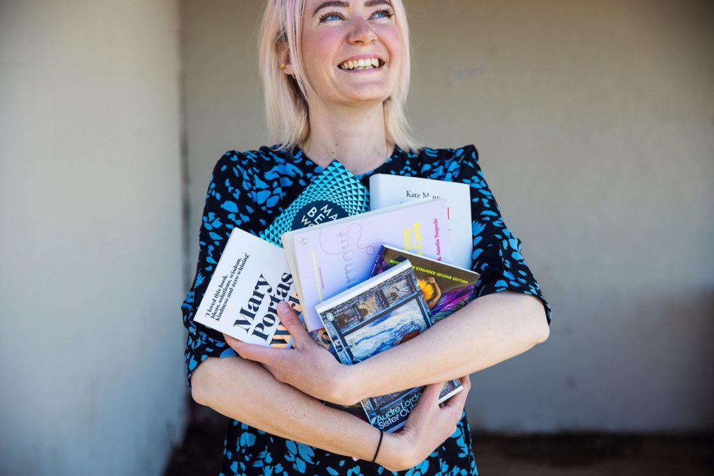 Keri, a pink-haired white woman, grins with an armful of books