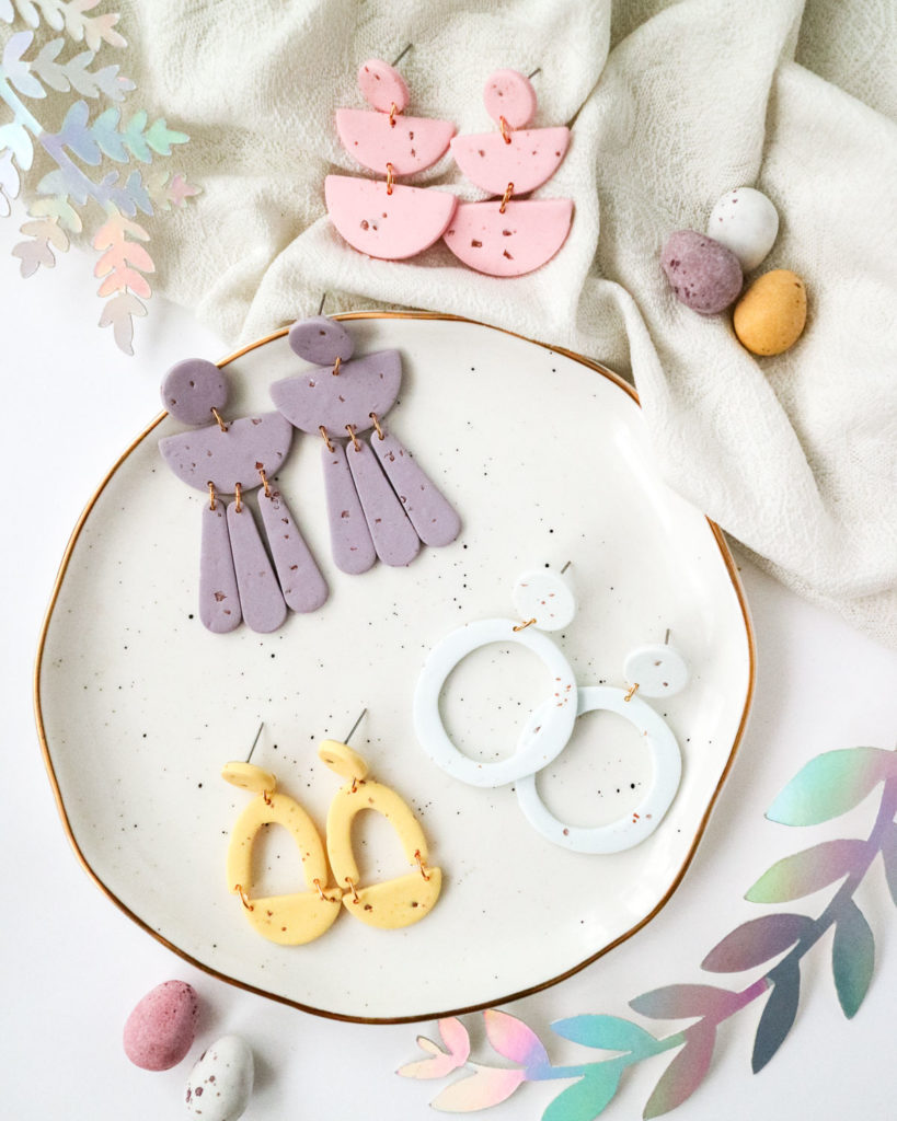 candy-coloured dangly earrings on a white plate