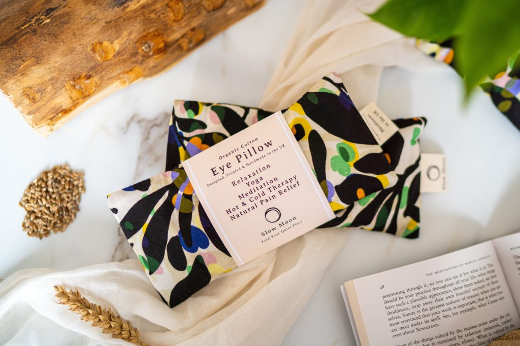 a flatlay of a patterned eye pillow next too a corn husk and a book.