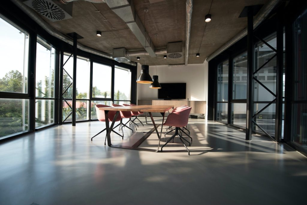 An open-plan meeting room with floor-to-ceiling windows and pink bucket chairs.