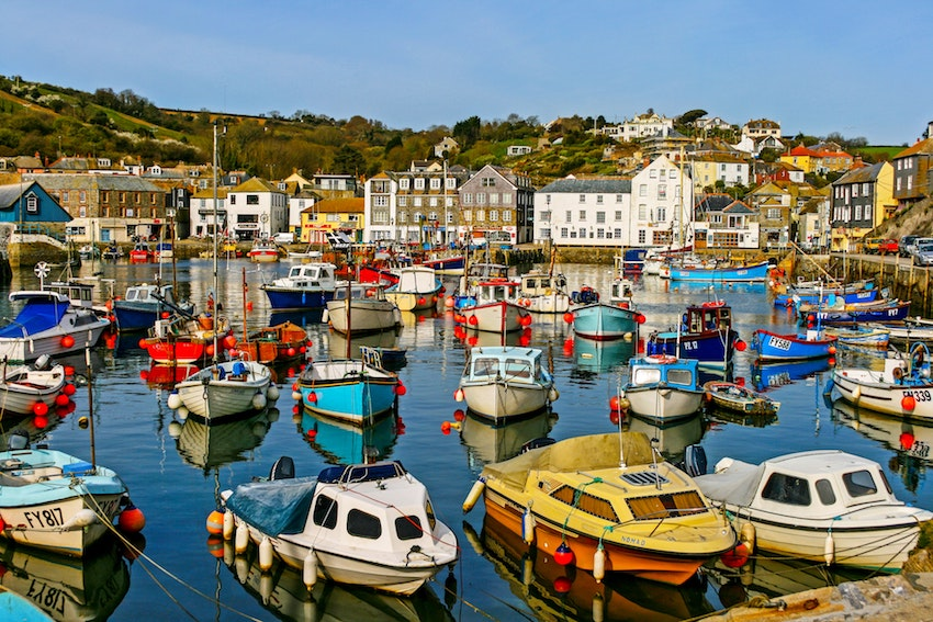 view across boats in harbour of Cornish fishing town