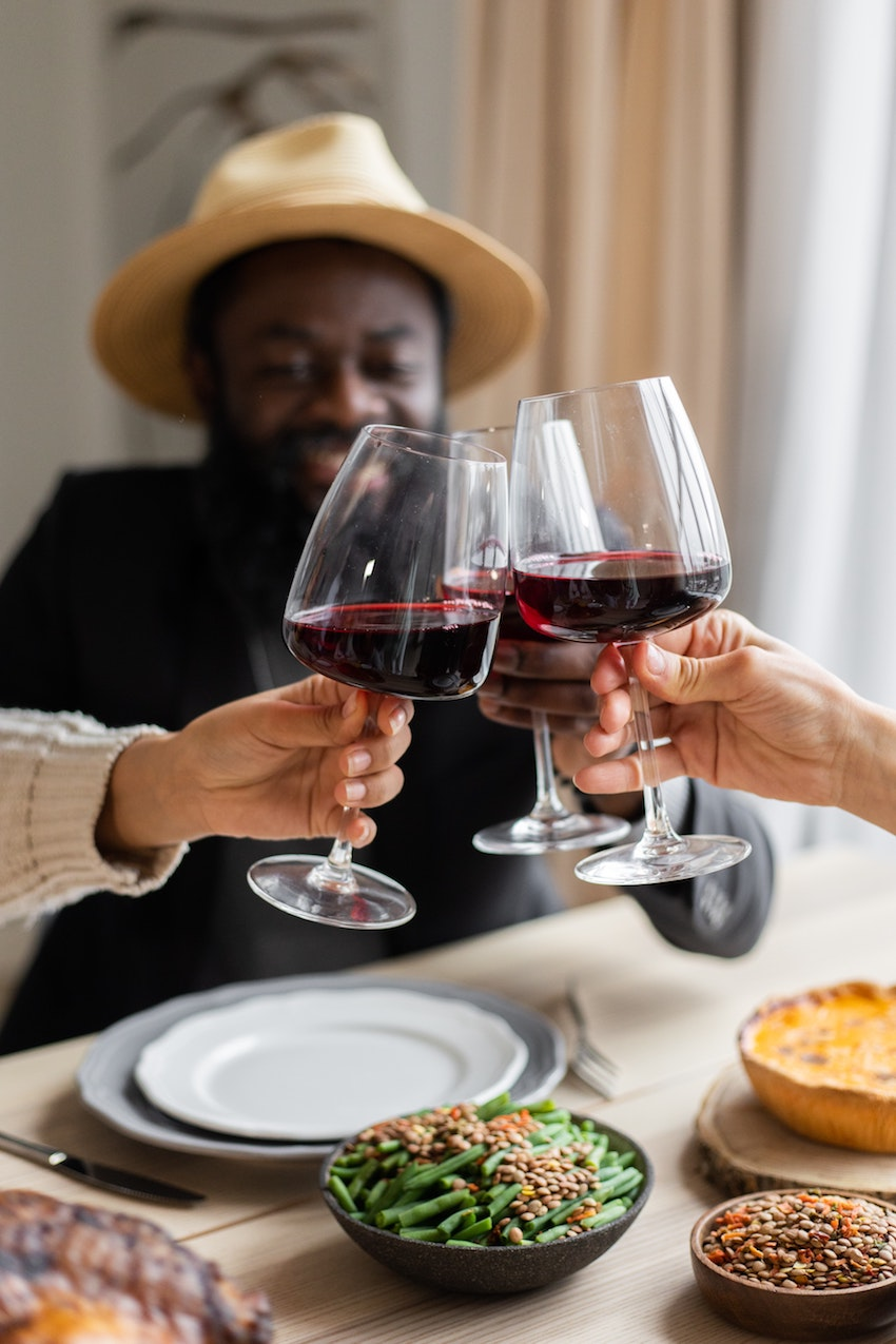 three people making a toast with red wine glasses with black man out of focus behind